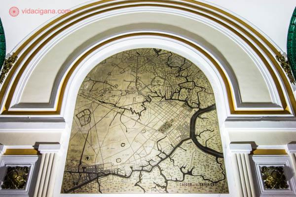 Foto de uma das paredes do prédio dos correios da Cidade de Ho Chi Minh, no Vietnã, projetado por Auguste Eiffel. Na parede vemos um arco adornado em dourado e um mapa de Saigon em seu meio.