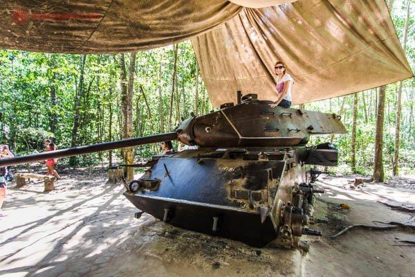 Mulher ruiva de cabelos curtos e usando óculos escuros sentada em cima de um tanque de guerra americano capturado pelos vietnamitas durante a Guerra do Vietnã. O tanque está no meio da selva e coberto por um toldo.