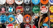 A feira de San Telmo, em Buenos Aires, na Argentina, com vários artesanatos sendo expostos para venda. Pessoal andam na frente do mural. O mural é muito colorido e toma a parede toda.