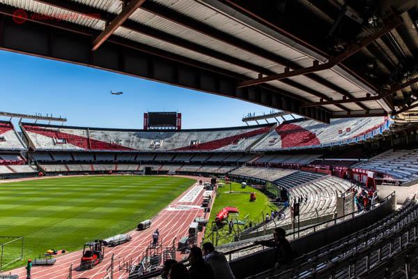 O que fazer em Buenos Aires: O estádio Monumental de Nuñez, que é o estádio do time de futebol argentino River Plate. A foto foi tirada da arquibancada, de onde é possível ver o campo verdinho lá embaixo. As arquibancadas são das cores do time, vermelho e branco. A foto é emoldurada com as arquibancadas de cima, que formam um teto. Lá no céu, ao longe, um avião.