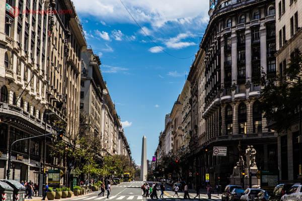 O Obelisco de Buenos Aires bem ao centro da foto, emoldurado por prédios dos dois lados. O céu está azul, com algumas poucas nuvens brancas. Algumas pessoas atravessam a rua na faixa de pedestres. Árvores são vistas do lado esquerdo da foto.