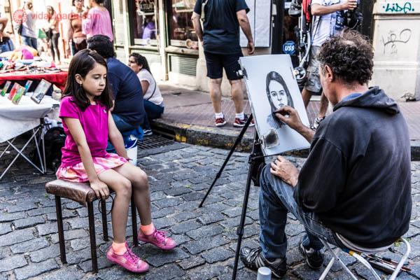 Uma menina está sentada em um banquinho enquanto seu rosto é desenhado por um artista de rua. Ela é morena e veste roupas rosas. O homem está desenhando um desenho em preto e branco em um cavalete.