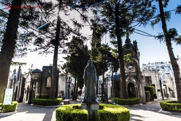 O interior do Cemitério da Recoleta, em Buenos Aires. Na foto vemos uma estátua central no meio de um mini gramado. Vários corredores com túmulos aparecem no fundo, com algumas árvores de todos os tipos. O céu está azul, e a foto foi tirada contraluz.
