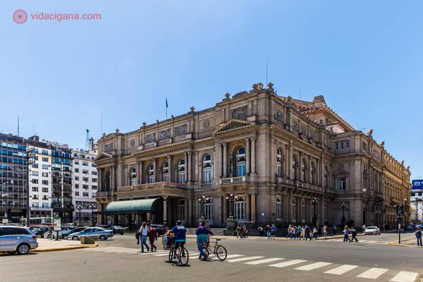 O Teatro Colón, em Buenos Aires, uma casa de ópera. O estilo é italiano, com 3 andares. Na rua, vemos algumas pessoas carregando bicicletas enquanto passam pela faixa de pedestres. O céu está azul e bem ensolarado.