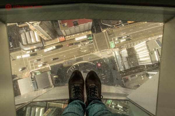 A cidade de Auckland vista do alto da Sky Tower, onde só os pés da fotógrafa aparecem, em cima de um chão de vidro de onde é possível ver as ruas e os carros lá embaixo.