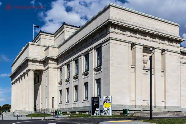 O Auckland Museum, um dos maiores museus da Nova Zelândia. Ele possui arquitetura clássica, com a fachada cheia de colunas e quinas pontudas. O céu está azul com algumas nuvens brancas.
