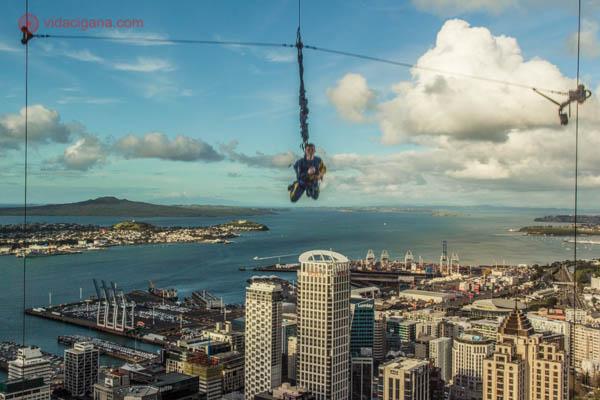O que fazer em Auckland: Um homem se jogando da Sky Tower, a maior torre da Nova Zelândia, em Auckland. Ele está preso por cabos e praticando esportes radicais. Ao fundo, a cidade de Auckland lá embaixo, com o mar e prédios altos. O céu está azul com nuvens brancas.