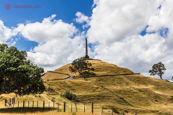 O que fazer em Auckland: One Tree Hill, um antigo vulcão que fica em Auckland, na Nova Zelândia. A colina possui um obelisco em seu topo e um caminho que vem até seu topo. A colina está coberta de grama seca numa coloração amarelada. O céu está azul com nuvens brancas. Árvores também são vistas no caminho. Na borda da foto é vista uma cerca de madeira.