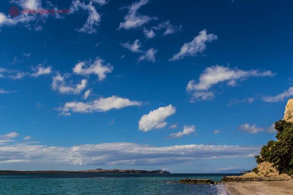 O que fazer em Auckland, a ilha de Waiheke - Uma pequena praia na Nova Zelândia, com uma pequena faixa de areia, com o mar claro, algumas rochas, um pedaço de terra ao fundo. O céu é azul com poucas nuvens brancas.