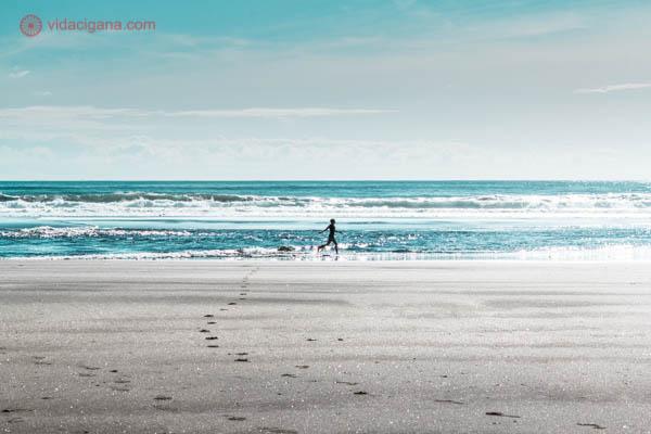 Uma mulher corre na frente do mar ao longe, onde apenas sua silhueta aparece. O céu está azul, o mar, azul esverdeado e a areia é clara.