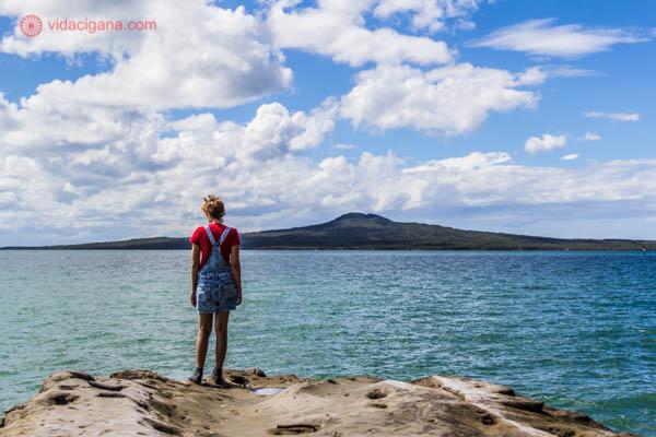 Uma mulher ruiva parada na borda de uma rocha, de frente do Rangitoto, um antigo vulcão em Auckland, na Nova Zelândia. Entre o vulcão e a rocha fica um mar azul. O céu está azul, com nuvens brancas.
