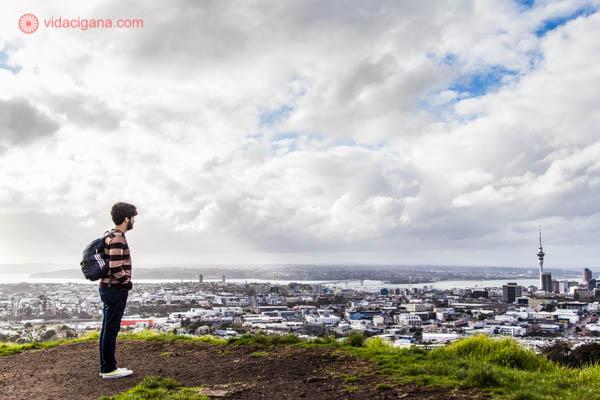 Homem em pé olhando para a cidade de Auckland, na Nova Zelândia, com a Sky Tower ao fundo. O céu está nublado.