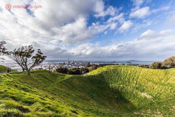 O que fazer em Auckland: O Mount Eden, o vulcão mais famoso de Auckland, a maior cidade da Nova Zelândia. Na foto vemos o vulcão extinto com sua cratera coberta de grama verde. Uma sombra se projeta para dentro da cratera. Uma árvore se encontra na borda da cratera. O céu está parcialmente nublado, com o canto direito azul e a esquerda com bastante nuvens. Ao fundo vemos a cidade de Auckland, com a Sky Tower, a maior torre do país.