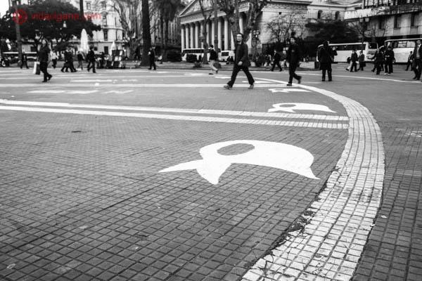 O chão da Plaza de Mayo, em Buenos Aires. A foto está em preto e branco, e algumas pessoas passam pela praça. O chão é feito de tijolinhos, é redonda e possui círculos brancos, e algumas faixas brancas também. Desenhos no formato de lenços brancos também são brancos.