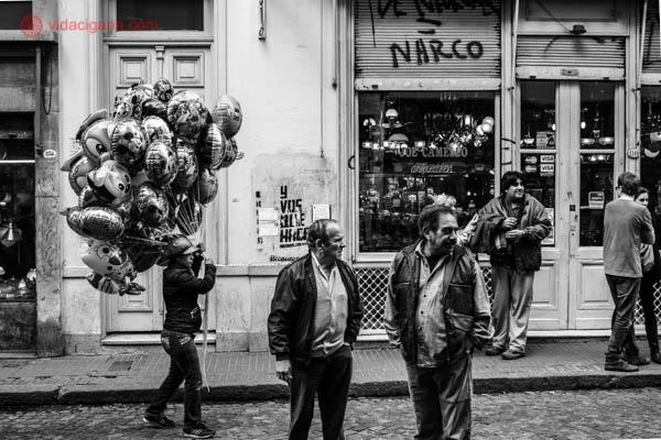 Uma rua no bairro de San Telmo, em Buenos Aires. A foto é em preto e branco. Três homens estão parados na rua, e um outro passa carregando balões. Atrás, lojas abertas.