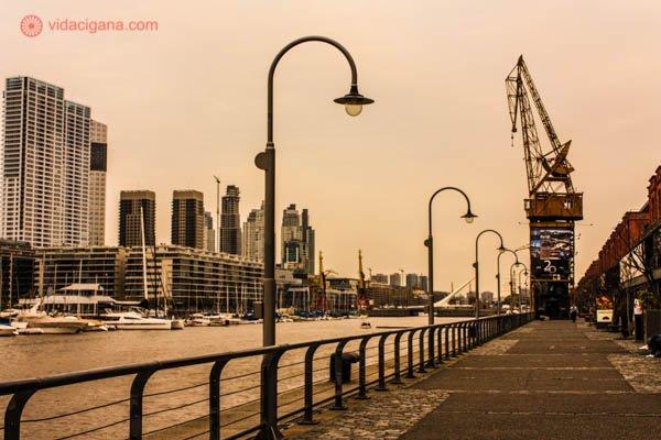O calçadão na orla do Puerto Madero, em Buenos Aires. Vários postes antigos se estendem pela margem, que é cercada por uma cerca baixa. Ao fundo, andaimes se encontram. O rio passa pelo lado esquerdo da foto, assim como vários prédios.