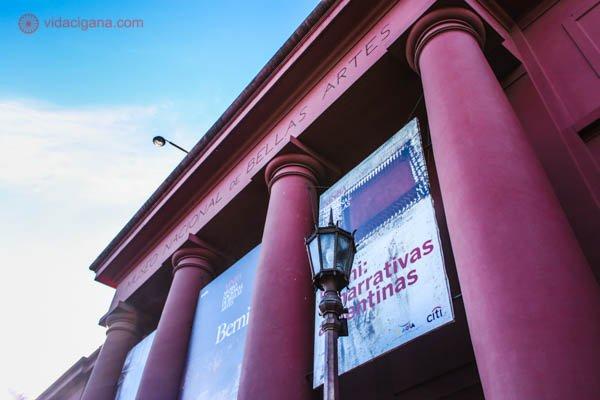 A fachada do Museo Nacional de Bellas Artes, em Buenos Aires. Um prédio no estilo clássico, cheio de colunas gregas, com as cores rosa choque, com várias placas informativas penduradas entre uma coluna e outra. O céu é azul. A foto foi tirada de baixo para cima.