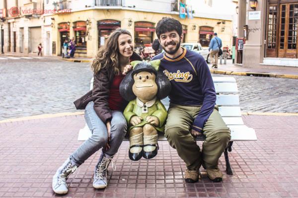 Uma mulher e um homem sentados em um banco do lado de uma escultura da Mafalda, em Buenos Aires.