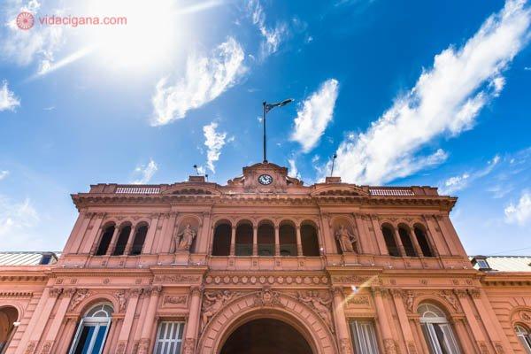 O que fazer em Buenos Aires: A Casa Rosada, em Buenos Aires, vista de baixo para cima. Um edifício antigo e elegante, na cor rosa, com a bandeira da Argentina tremulando em um mastro no seu topo. Várias sacadas se espalham pelo prédio. O céu está azul com algumas nuvens brancas.