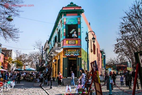 O Caminito, em Buenos Aires. Um prédio triangular de várias cores se encontra no meio da foto. Pessoas andam por todos os lados. O céu está azul.