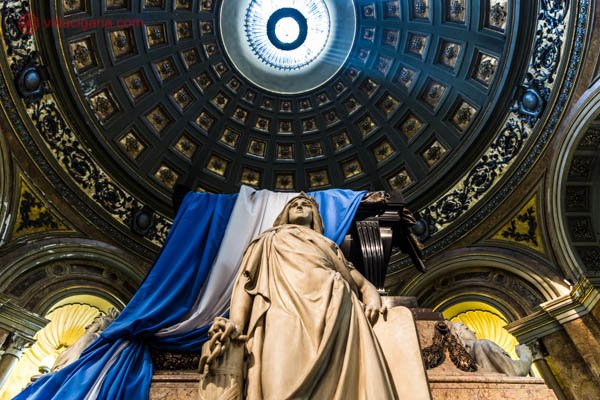 O interior da Catedral Metropolitana de Buenos Aires, especificamente, o túmulo de San Martín. Na foto vemos uma estátua branca de uma mulher clássica. Logo atrás dela, um enorme e alto caixão com a bandeira da Argentina sobre ele. A bandeira da argentina tem as cores azul e branca. No teto, uma linda cúpula totalmente decorada se encontra, com uma luminária em seu meio.