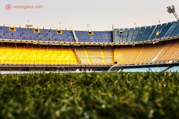 O que fazer em Buenos Aires: O estádio La Bombonera, estádio do time de futebol argentino Boca Juniors. A foto foi tirada da altura do gramado, então é possível ver em primeiro plano a grama desfocada, e lá ao longe, as arquibancadas com as cores do time, azul e amarelo.