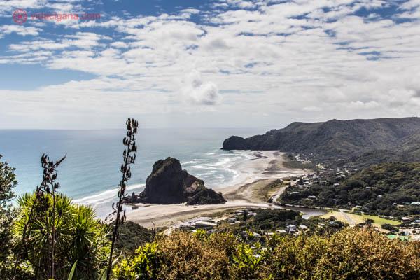 Onde ficar em Auckland - A praia de Piha, em Auckland, na Nova Zelândia, com seu mar azul, a Lion's Rock no meio. Emoldurada por uma vegetação verde e céu azul, com nuvens brancas.