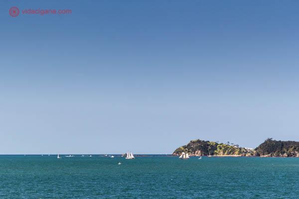 Mar azul e céu azul sem nenhuma nuvem, com veleiros no mar. Do lado direito da foto, um cabo alto.