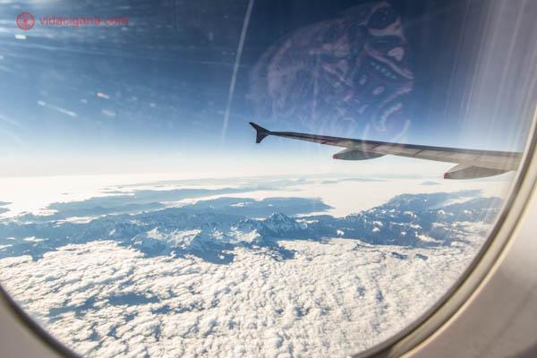 Vista da janela de um avião, com o céu azul, nuvens lá embaixo entre montanhas escuras. Da janela dá para ver a asa do avião.