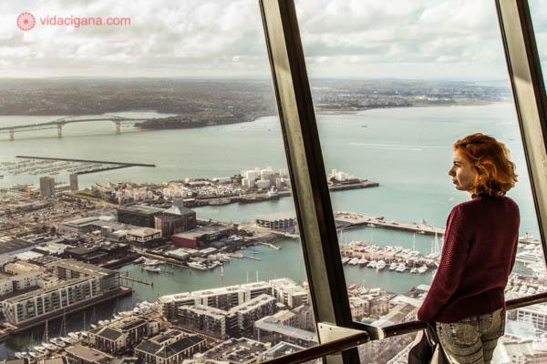 Mulher ruiva usando um suéter vinho no topo da Sky Tower, em Auckland, na Nova Zelândia. Ela olha para fora de uma janela enorme com a vista para a cidade lá embaixo, com a baía aos seus pés. O céu está nublado.