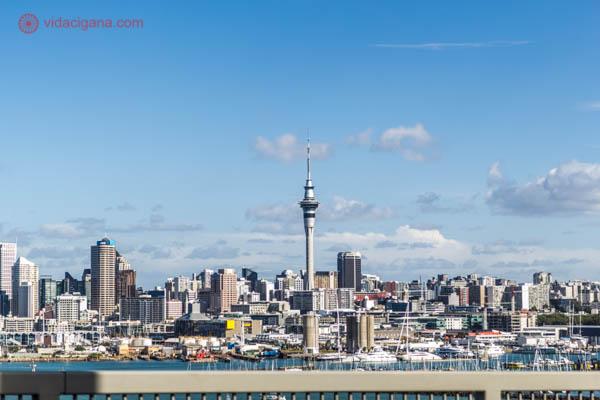 A cidade de Auckland vista do outro lado da baía, com todos os seus prédios, com destaque ao Sky Tower, a torre mais alta do país. O céu está azul, com algumas poucas nuvens brancas. A cidade está na beira da água.