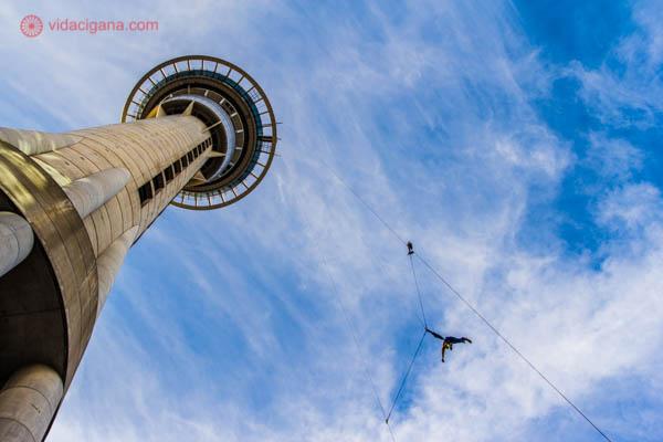 A Sky Tower, no centro do Auckland, na Nova Zelândia, vista de baixo para cima. O céu está azul com algumas nuvens brancas. Um homem se joga da torre, praticando esporte radical, que é bem comum na Nova Zelândia. Ele está preso por cabos de aço. A torre tem o topo arredondado.