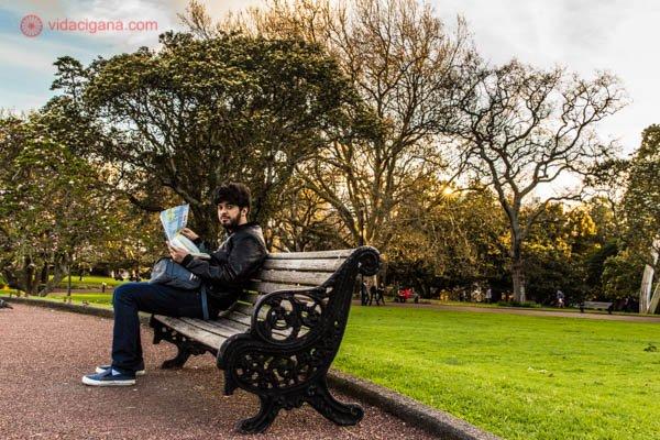 Homem sentado em banco de madeira no Albert Park, em Auckland, na Nova Zelândia. Ao redor, muitas árvores e verde. O home está vendo um mapa da cidade.