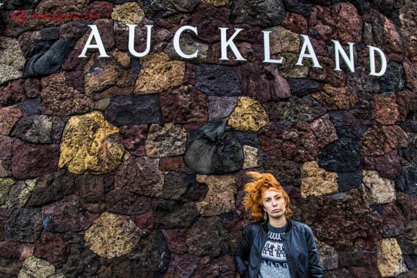 """Uma mulher ruiva com os cabelos ao vento na frente um um muro de pedras coloridas com letras brancas formando a palavra """"Auckland"""", em Auckland, na Nova Zelândia."""