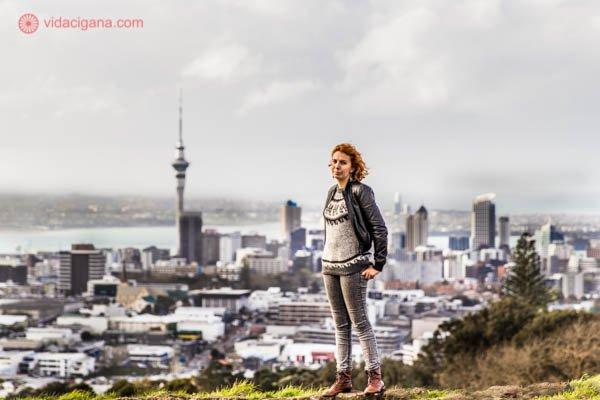 Mulher ruiva em cima da borda do vulcão Mount Eden, em Auckland, na Nova Zelândia, com vista para a cidade lá ao fundo, com a Sky Tower, uma torre pontiaguda, se destacando lá ao longe. O céu está nublado. A cor predominante na foto é o cinza.