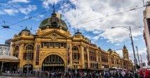 O prédio do Flinders Street Railway Station, em Melbourne, na Austrália, com sua cor amarela e sua arquitetura antiga. Com sua cúpula verde e estilo ligeiramente indiano, o prédio fica numa área bem movimentada, onde várias pessoas cruzam as faixas de trânsito bem em frente. O céue stá azul com algumas nuvens brancas e algumas cinzas.