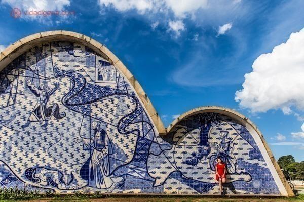 A igreja da Pampulha com seus enormes painéis produzidos por Cândido Portinari. Todos em tons de azul e branco. Uma mulher vestida de vermelho se destaca na foto e está encostada no mural. O céu é azul com algumas nuvens.