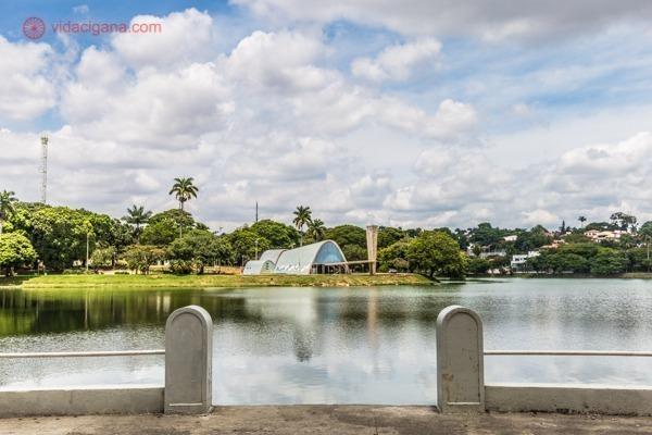 A Lagoa da Pampulha, em Belo Horizonte, com a Igreja de São Francisco de Assis ao fundo. O céu está azul e ao fundo é possível ver muito verde.