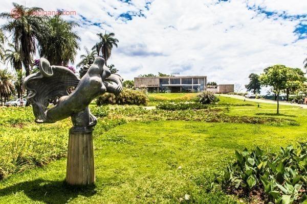 O Museu de Arte da Pampulha, em Belo Horizonte, prédio projetado por Oscar Niemeyer. Ao fundo o prédio de encontra no topo de uma colina, com um enorme gramado verde. Em primeiro plano, uma estátua. O céu está azul com várias nuvens brancas.