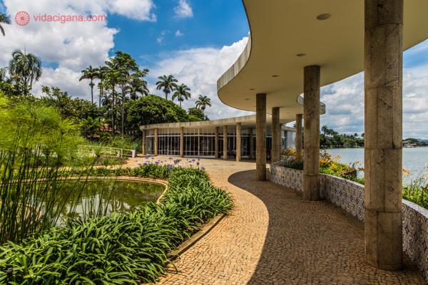 A Casa do Baile, em Belo Horizonte, prédio projetado por Oscar Niemeyer. Suas curvas são fascinantes, com sua marquise sustentada por várias colunas, seu jardim bem cuidado e verde, com uma calçada de pedrinhas laranjas. O céu é azul com algumas nuvens brancas e ao fundo palmeiras imperiais se sustentam.