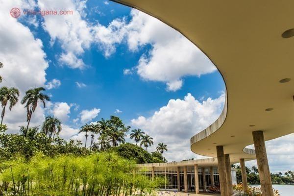A Casa do Baile, parte do conjunto arquitetônico da Pampulha, em Belo Horizonte, projetado por Oscar Niemeyer. Com suas curvas maravilhosas e seu lindo jardim, encanta a todos. O céu está azul e as nuvens brancas.