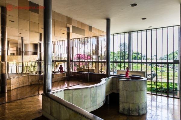 O Cassino da Pampulha, atual Museu de Arte da Pampulha, em Belo Horizonte, projetado por Oscar Niemeyer. Cheio de espelhos cor de ocre, de suas enormes janelas é possível ver o lindo jardim lá fora. Uma mulher de vermelho se destaca na foto.