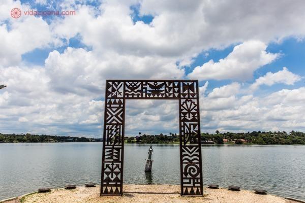 A Praça de Iemanjá na Lagoa da Pampula, com seu lindo portal com os símbolos dos orixás e a estátua de Iemanjá ao fundo. A lagoa se encontra ao fundo, o céu está azul com várias nuvens brancas.