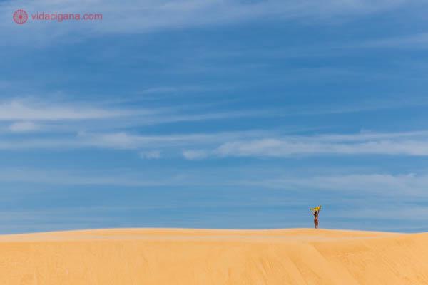 Mulher nas dunas do delta do São Francisco segurando uma canga no ar enquanto ela balança com o vento. A areia é clara e o céu azul.