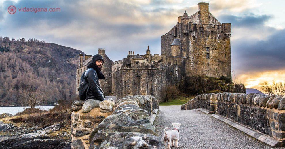 Homem vestindo jaqueta preto e gorro descansa sobre mureta de pedra enquanto segura pela correia a coleira de um cachorro branco da raça scnauzer. A cena ocorre em frente ao Castelo de Eilean Donan, próximo à ilha de skye nas Highlands da Escócia.