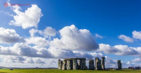 O monumento de Stonehenge, na Inglaterra, feito de blocos de pedra do período neolítico. O círculo de pedra se encontra em um campo de grama verde imenso. O céu está muito azul, com nuvens brancas que voam pro lado esquerdo da foto.