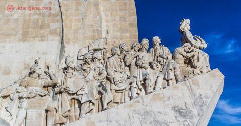 Detalhe do lado leste do Padrão dos Descobrimentos, em Lisboa, com vários navegadores e personalidades importantes para a expansão marítima portuguesa. O monumento é feito de pedra, e o céu ao fundo é azul.
