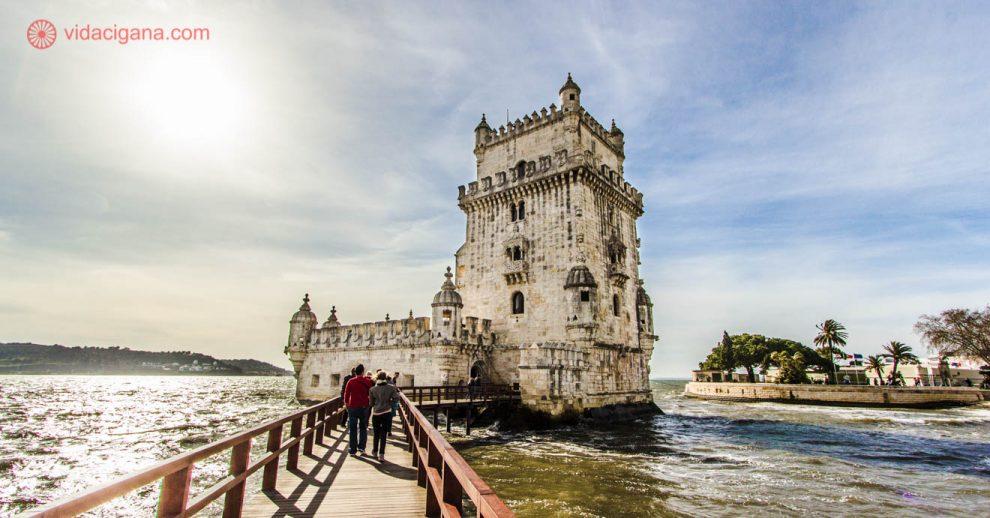 A Torre de Belém, em Lisboa, com o sol do lado esquerdo da foto, com pessoas caminhando por sua ponte, indo em sua direção. O céu está azul com nuvens pinceladas brancas. A Torre é branca.