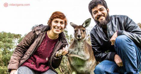 Um casal na Austrália posando com um canguru em uma reserva ecológica perto de Perth. Eles usam roupas de frio e estão muito felizes segurando a pata do animal. O dia está nublado e frio.
