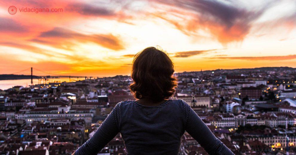 Uma mulher de costas observando um incrível pôr do sol visto do Castelo de São Jorge, em Lisboa. O céu está pintado de inúmeras cores que vão do laranja ao roxo, passando pelo amarelo e pelo rosa. Lá embaixo, as inúmeras casas e prédios de Lisboa estão se acendendo de acordo que a noite chega.